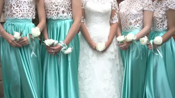 Bride in gorgeous dress and her four maids in green dresses are holding boutonnieres of white peonies wrapped with silver ribbons.