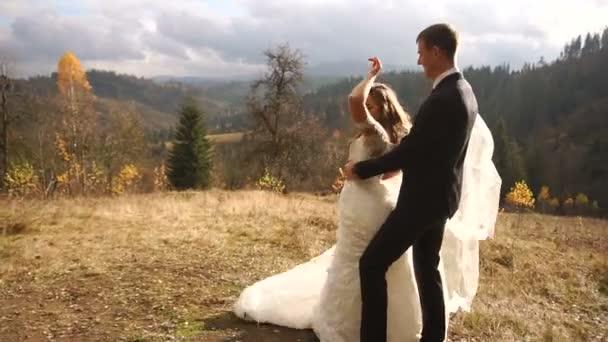 Tanzendes Brautpaar in den bezaubernden goldenen Bergen. Glückliche Hochzeitsmomente.