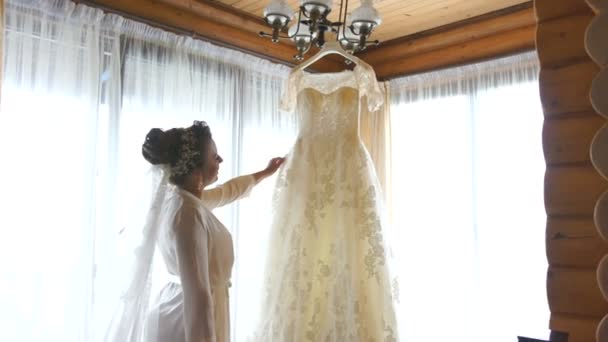 Charming bride in silk robe and veil on her hair is looking at her ...