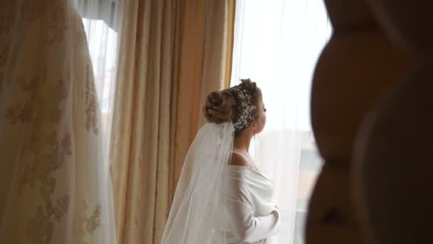 Néz az ablakon keresztül a fehér selyem köntöst a elegáns szőke menyasszony hátulnézet.