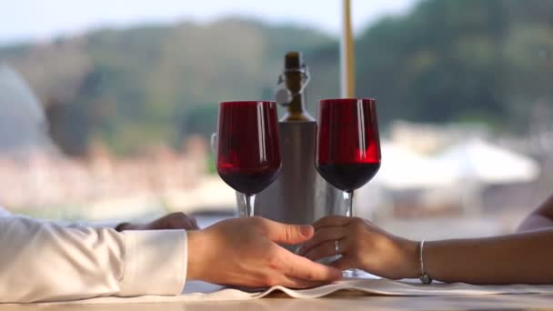 Loving couple is having romantic date. They are tenderly holding hands at the background of the wineglasses. No face.