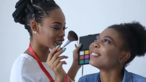 Happy african make-up artist is applying powder on the face of the amazing african model with pretty smile.