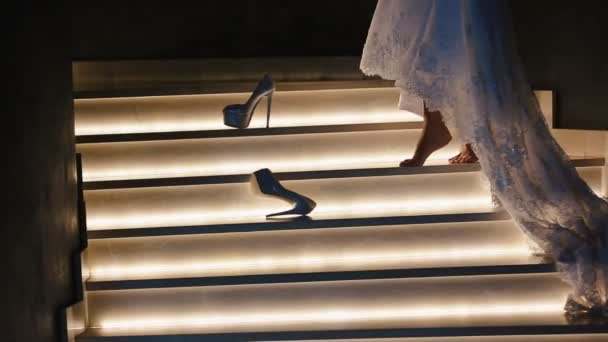 Lying wedding high heels on the lighting stairs. Bride in the long dress is walking on the tiptoes. No face.