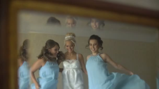 Reflection in the mirror of three charming ladies. Wonderful bride and her two bridesmaids are celebrating the marriage.