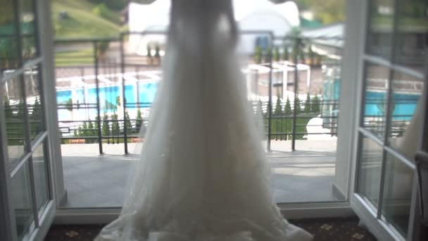 Rear view of the stylish blonde bride in the wonderful weil and long wedding dress walking on the terrace.