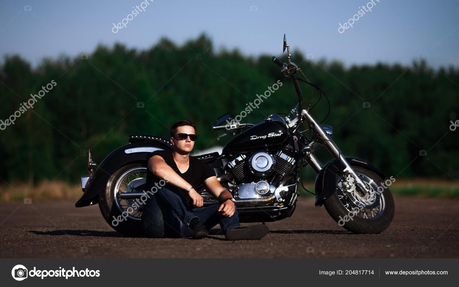 b9b7167039 Hombre guapo motero en copas sentado en su moto. Fondo de camino de campo —