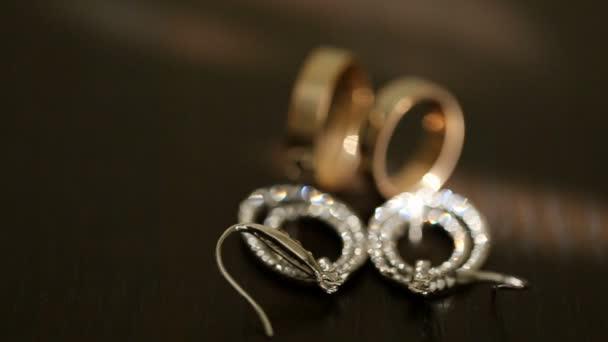 Pohled na detail zlaté snubní prsteny a svatební Náušnice stříbrné s diamons u stolu.