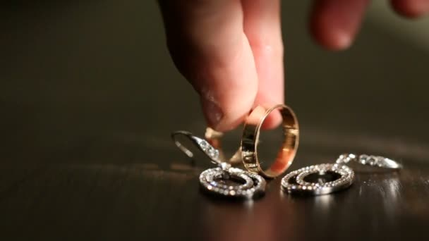 Unknown male hand is putting the bridal golden wedding ring near the grooms one. Wedding composition consisting of rings and silver bridal earrings with diamonds.