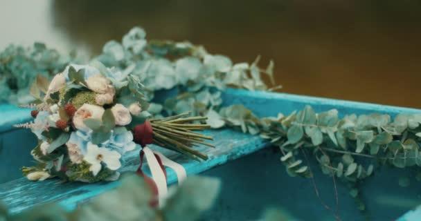 Nádherné kytice barevné různých zabalené s červenými a bílými stuhami leží na staré modré rustikální boat zdobené s bylinkami. 4k
