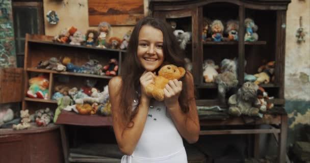 Mosolygó 10 éves gyönyörű lány a gazdaság egy mackó teli kertben a régi játékok. 4k.