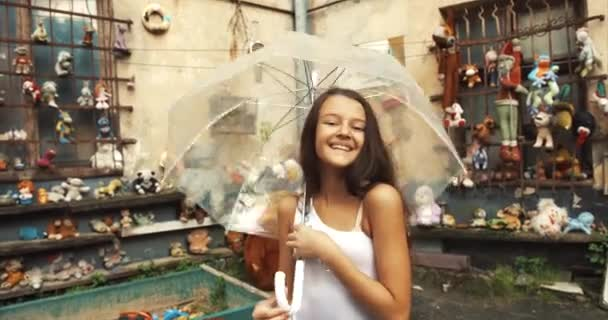 Nagyon vidám kislány szép mosoly és hosszú, sötét haj, szórakozás a kert tele régi játékok. Ő a spinning be ng az átlátszó esernyő. 4k.