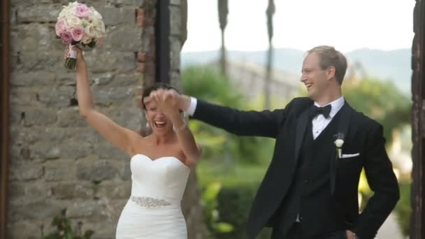 Gorgeous cnewlyweds are happy to get married. Handsome groom is tenderly spinning round his bride and kissing outdoor.