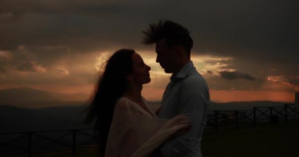 Pryč s větrem. Obrázek krásný pár objímaly něžný a líbání stoje na kopci s červenými a šedými suvlaki nad nimi