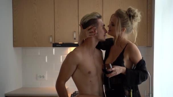 Csinos fiatal ember meztelen felsőtestét ölelést pályázati szexi fiatal nő luxus fekete fehérnemű, míg iszik bort a konyhában