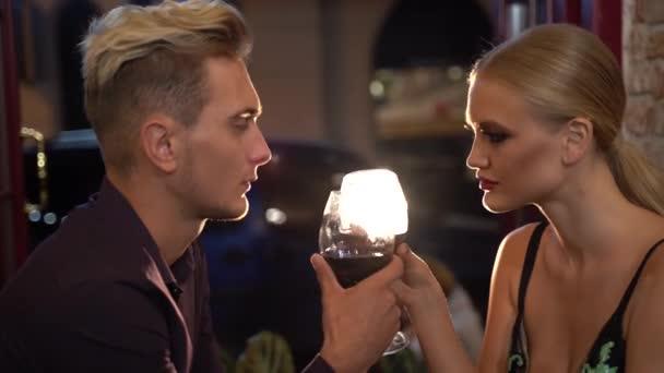 Romantická atmosféra kolem pěkný muž a žena pití vína v restauraci a při pohledu na sebe s vášní