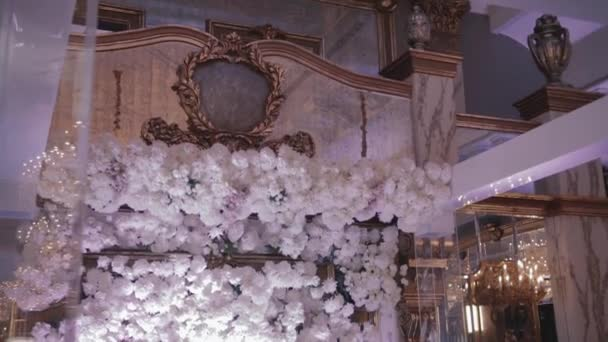 Restaurant wedding decor and arrangements. Cloud of white roses and chrysanthemums hangs over head table for newlyweds at the wedding reception