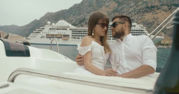 Couple in love relaxing on the yacht. Man and woman dressed in white clothes hug each other tender enjoying their trip on yacht