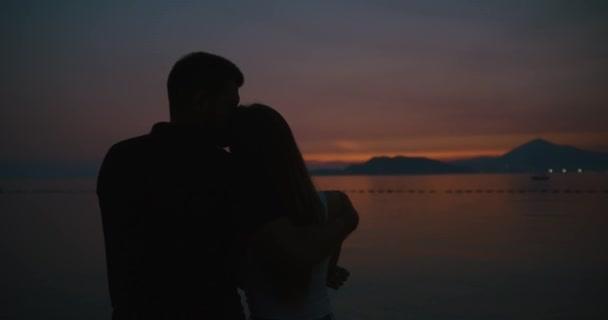 Liebesgeschichte auf den Sonnenuntergang. Sillhouetes von Mann und Frau küssen einander zärtlich, während sie an der Küste in den Strahlen der Abendlicht stehen