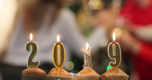 Nový rok oslava. Košíčky se svíčkami v číslech 2019 stát na stole před Veselá společnost slaví Nový rok před vánoční stromeček