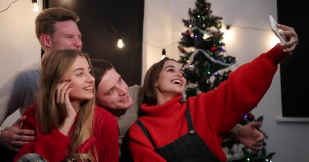 New Year celebration. Two young couples taker a selfie on the smartphone sitting before a Christmas tree