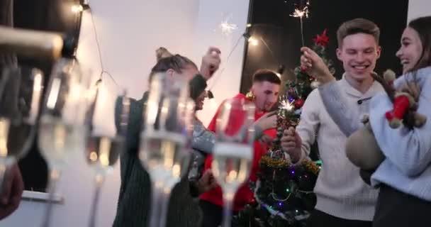 Nový rok oslava. Člověk vylévá šampaňské v brýlích a tanec mladých lidí na pozadí před vánoční stromeček. 4k