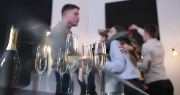 Nový rok oslava. Lidé tancují na pozadí, zatímco fotoaparát zaostří na šampaňské flétny