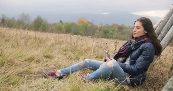 Freizeit in den Bergen. Herbstberufungen. attraktive brünette Frau in Jeans und Lederjacke sitzt auf dem Hügel und blickt nachdenklich auf nebelbedeckte Berge.