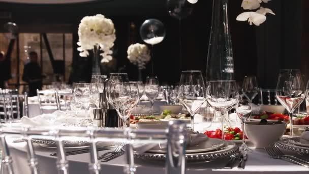Empfang, Feier im Restaurant. große runde weiße Tische mit weißen Blumen und leckeren Essensständen in der lichtdurchfluteten Halle