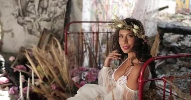 Konceptuální Střelba. 4 k. žena s dlouhými tmavými vlasy, oblečená stejně jako nymfa leží na staré posteli mezi kvetoucí růžové květy a hau a usmívá se dívá přímo do kamery.