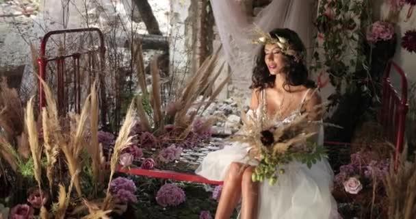 Konceptuální Střelba. 4 k. žena s dlouhými tmavými vlasy, oblečená stejně jako víla sedí na staré posteli mezi kvetoucí růžové květy a hau a usmívá se dívá přímo do kamery