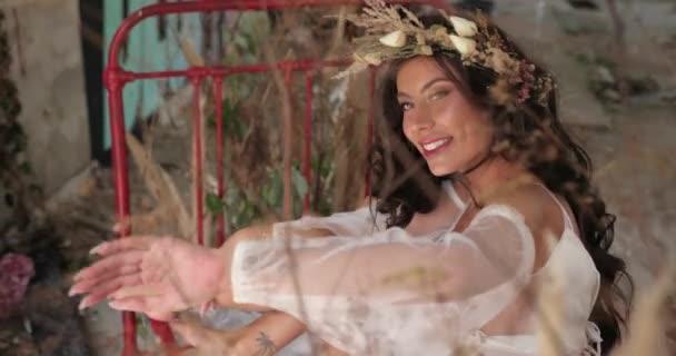 Konceptuální Střelba. 4 k. žena s dlouhými tmavými vlasy, oblečená stejně jako nymfa leží na staré posteli mezi kvetoucí růžové květy a hau a usmívá se dívá přímo do kamery