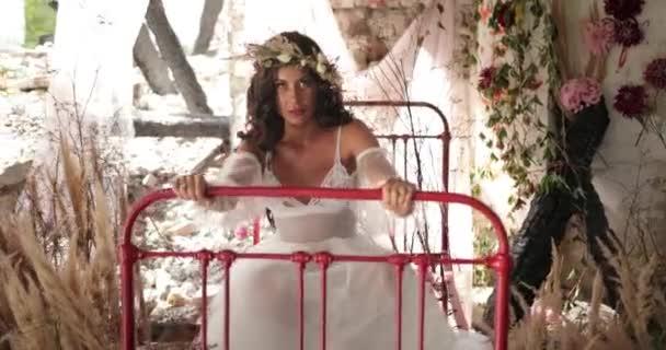 Konceptuální Střelba. 4 k. žena s dlouhými tmavými vlasy, oblečená stejně jako víla sedí na staré posteli mezi kvetoucí růžové květy a hau a usmívá se dívá přímo do kamery. Vztek, agresivní