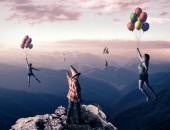 Fotografie Mladý muž se na vrcholu hory poukazují na lidi s balónky vysoko nad horami. Pojem sen.