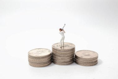 Coins and miniature golfers. concept of betting golf.