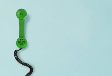Telephone receiver laying on blue background