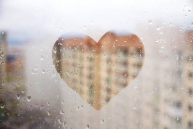 Heart painted on glass wet window in city