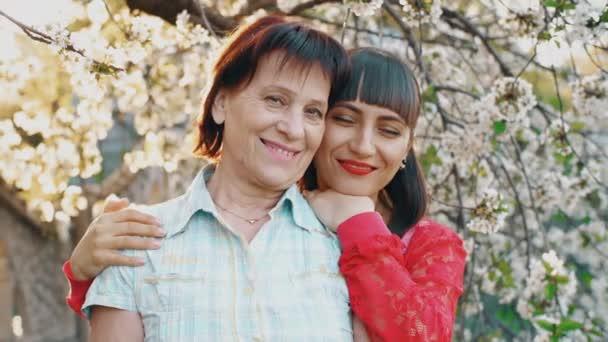 Seniormutter und ihre erwachsene Tochter umarmen sich, blicken in die Kamera und lächeln