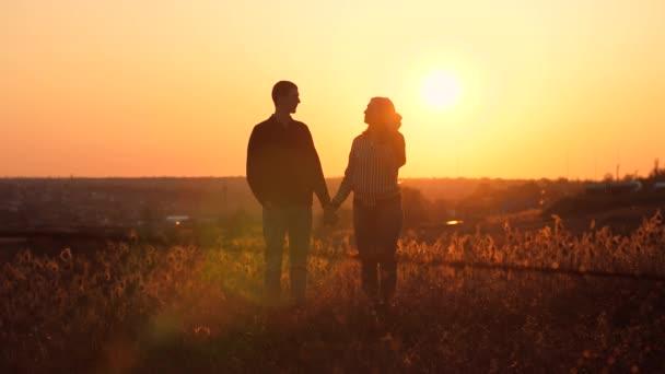 Muž a žena líbání při západu slunce
