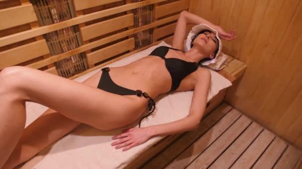 Žena leží na dřevěné lavici v sauně