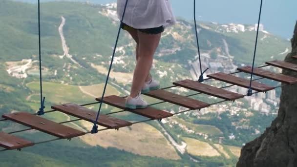 Woman walking by suspension bridge