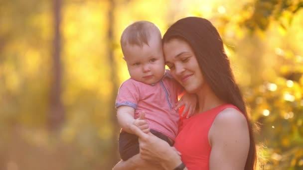 Usmívající se matka s dítětem při západu slunce