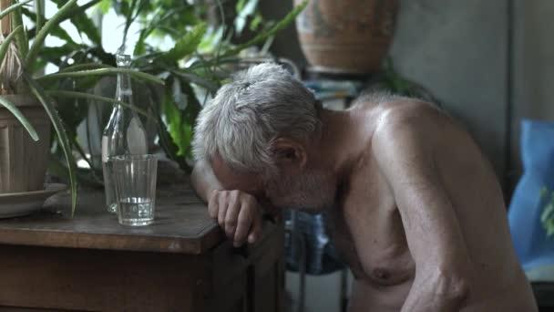 Betrunkener alter Mann schläft am Tisch