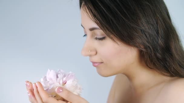 Woman smelling flower on white background