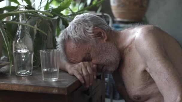 Depressiver betrunkener Mann am Tisch