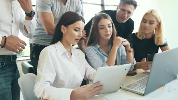 Group of coworkers working together with laptop