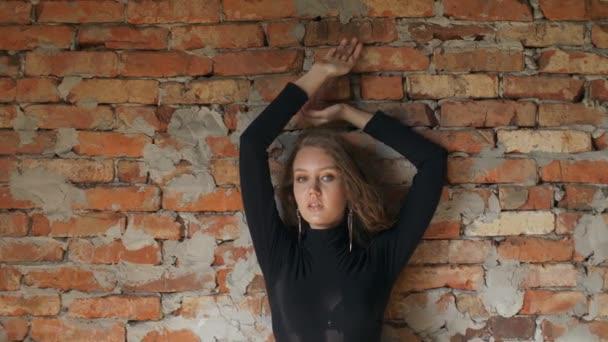mladá žena pózuje proti cihlové zdi