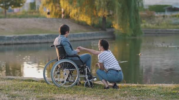 Frau und Mann im Rollstuhl füttern Enten
