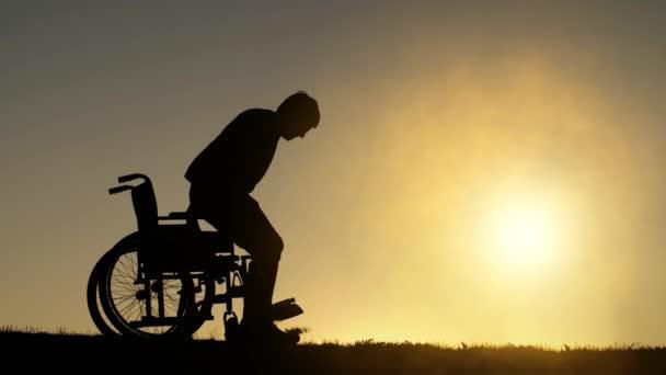 Behinderter steht aus dem Rollstuhl auf und hebt die Hände