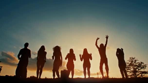 Skupina mladých lidí skákajících při západu slunce