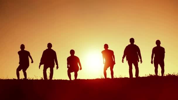 Fröhliche Freunde springen bei Sonnenuntergang auf